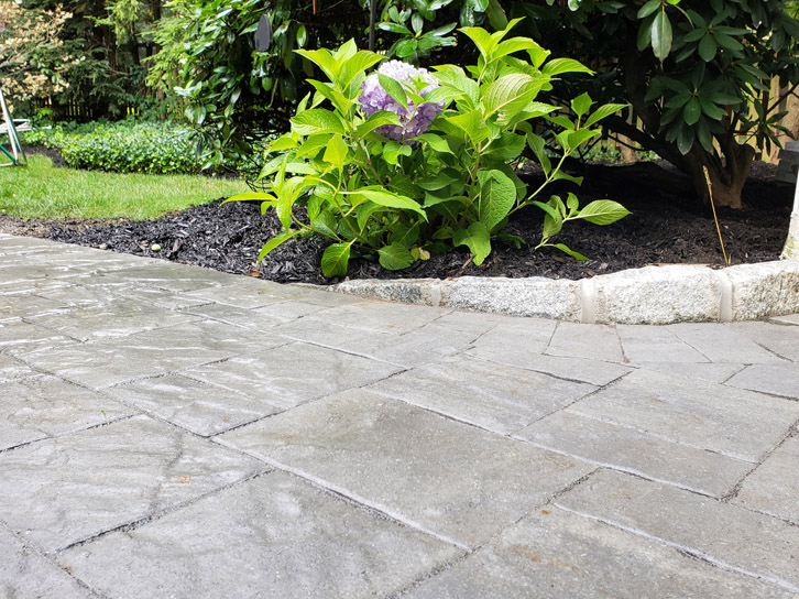 beautiful hardscaping in stone next to a well-landscaped garden in Cliffside Park NJ
